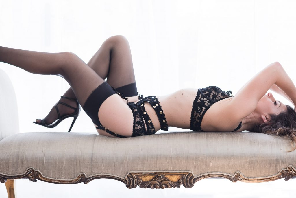 Boudoir Photography showcasing lace lingerie matching suspenders and stockings basking in back lit light