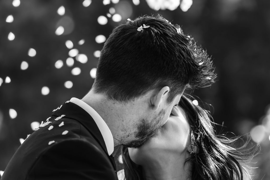 Wedding Photography featuring Black and white image of Bride and Groom kissing under falling white cherry blossom