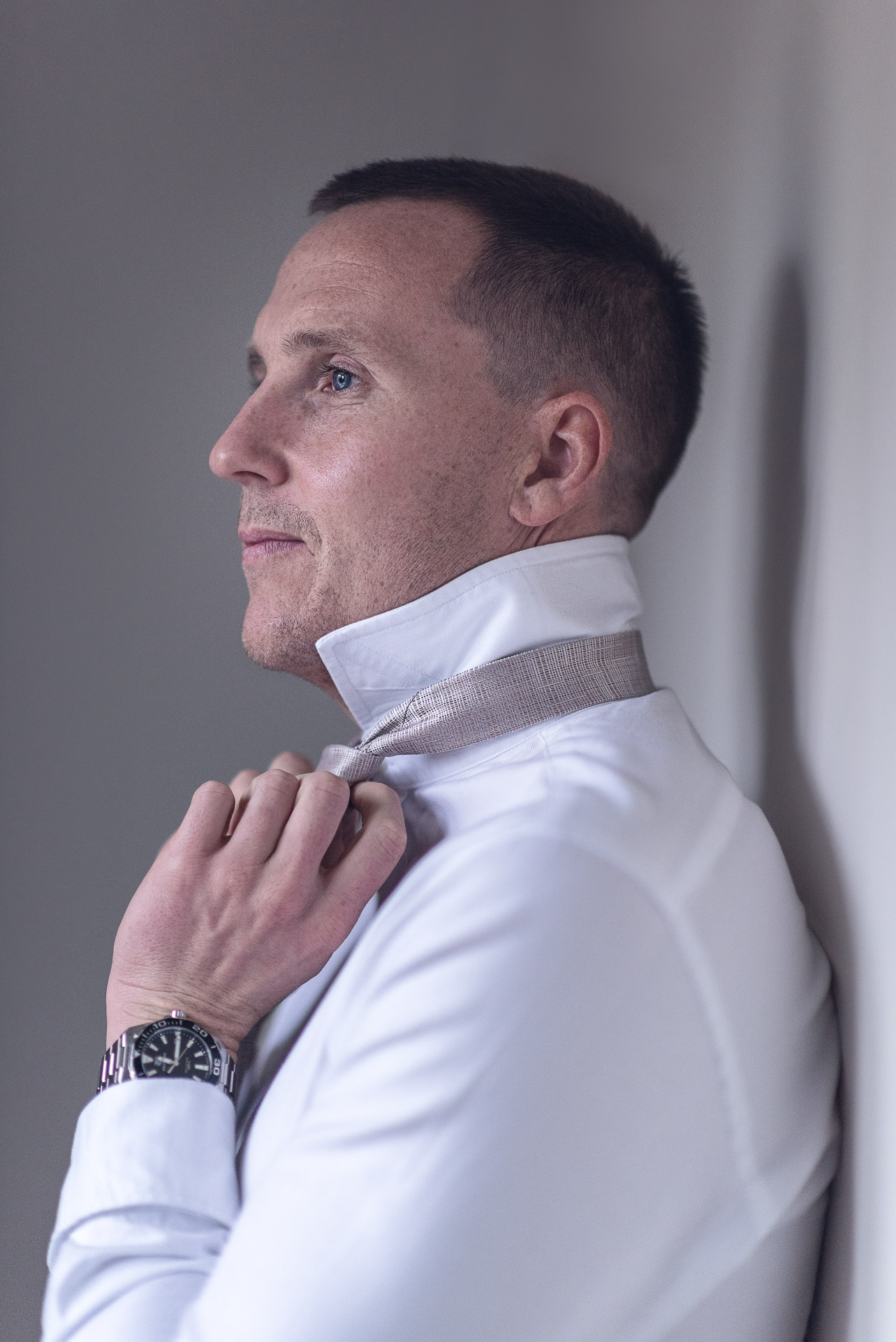 Wedding Photography featuring groom preparation adjusting tie