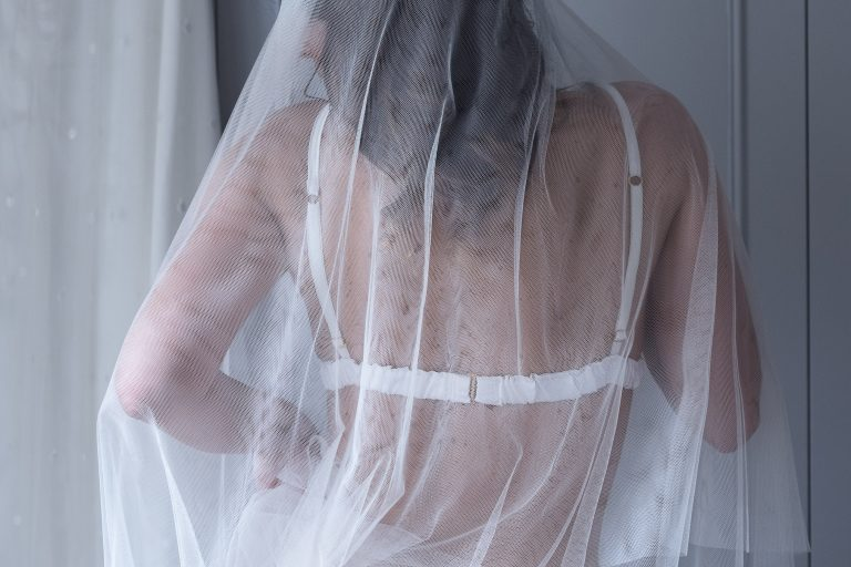 Bridal Boudoir photography featuring bride showcasing designer lingerie and veil