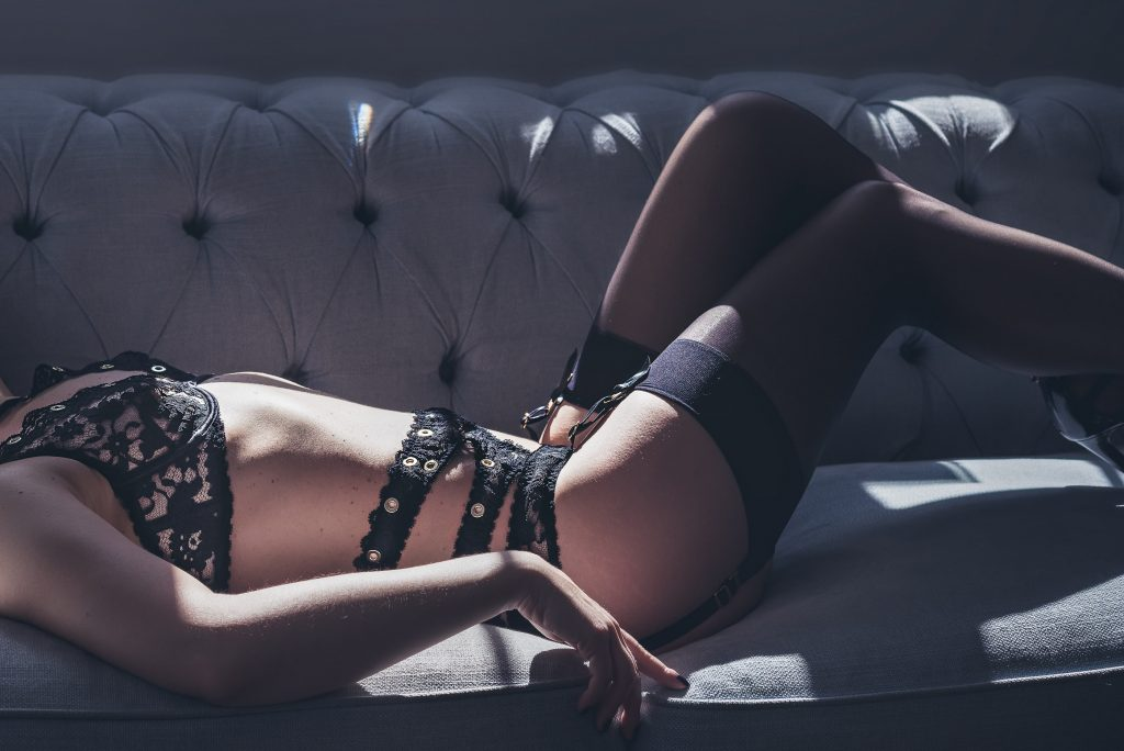 Boudoir Photography showcasing lace lingerie matching suspenders and stockings basking in shafts of light