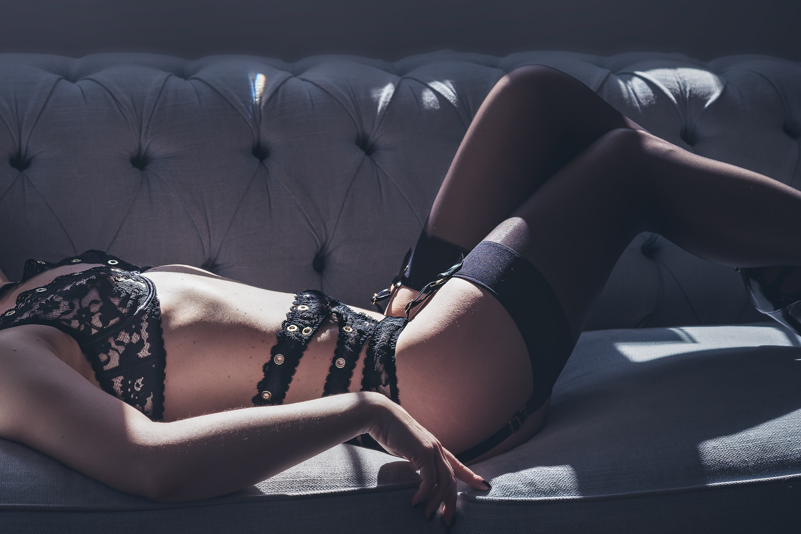 Boudoir Photography showcasing designer lace lingerie, suspenders and stockings laying in shafts of light