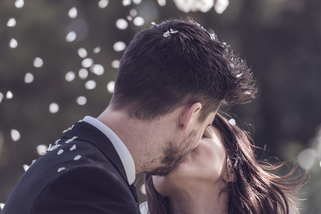 Wedding Photography featuring bride and groom kissing under falling cherry blossom